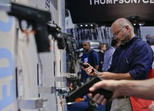 Photo by: Julie Jacobson Trade show attendees examine various hand guns in the Smith & Wesson display booth at the Shooting Hunting and Outdoor Tradeshow, Tuesday, Jan. 14, 2014, in Las Vegas. (AP Photo/Julie Jacobson)